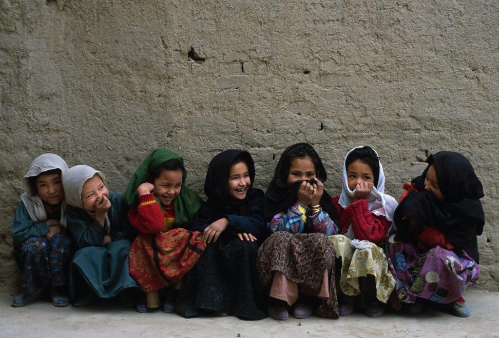Girls sit in a row against a wall at their school, Dasht-e-Barch
